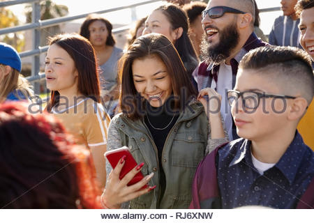 Happy woman using smart phone in bleachers during baseball game - Stock Photo