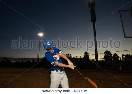 Baseball player with bat practicing swing on field at night - Stock Photo