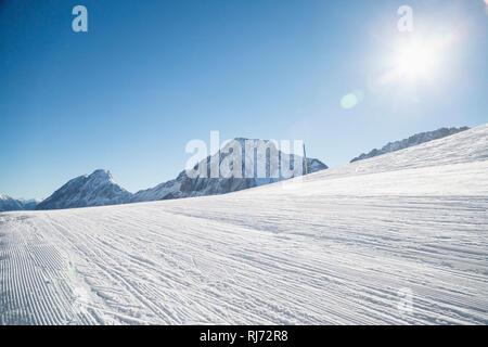 Blick in die Sonne, Spuren auf der Skipiste, - Stock Photo