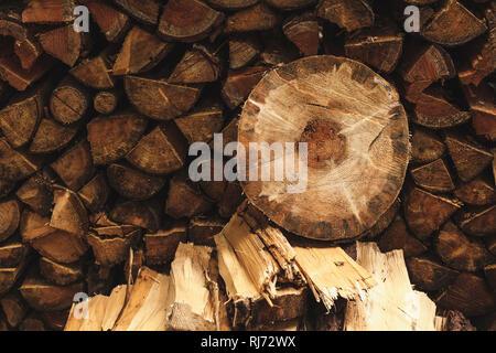 Eine runde Holzscheibe liegt auf einem Stapel Feuerholz,
