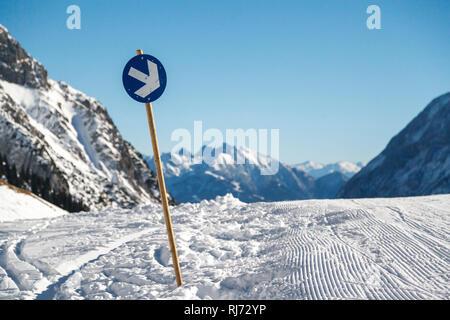 Spuren der Schneeraupe und ein Wegweiser auf der Skipiste, gepflegte Abfahrt, - Stock Photo