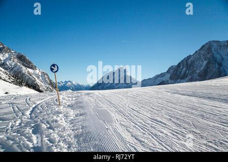 Spuren der Schneeraupe und ein Wegweiser mit Pfeil auf der Skipiste, gepflegte Abfahrt, - Stock Photo
