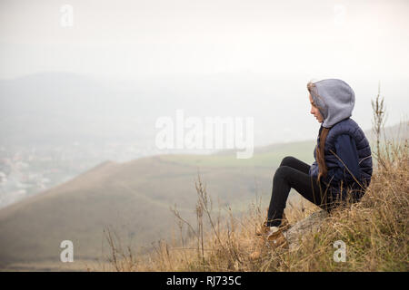 active healthy little girl in sleveless jacket and hood sitting on mountain slope during hiking - Stock Photo