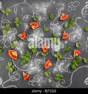 Tomaten mit Basilikum auf mit Kreide bemalter Tafel - Stock Photo