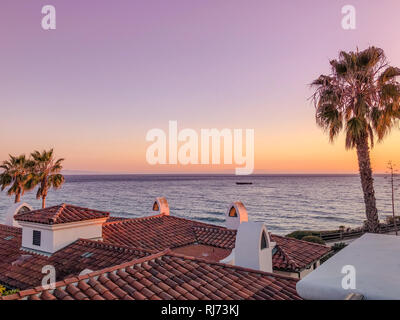 Sunset over PAcific ocean near Santa Barbara, USA; rooftops and palm trees - Stock Photo