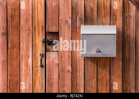 Grey mail box with Post sign on it  hanging on new wooden wall, door with metal handle and lock - Stock Photo