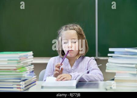 Schülerin, 7 Jahre alt, lesend, zwischen zwei Stapeln Bücher, vor einer Tafel - Stock Photo