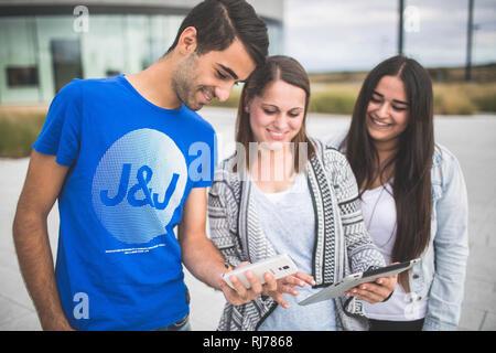 Drei Jugendliche mit Tablet und Smartphone unterwegs