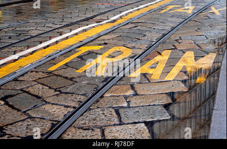 Cobbled road in central Milan showing lane markings for Tram and taxi, Milan, Lombardy, Italy. - Stock Photo