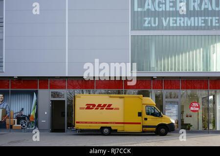 Ein Paketzusteller und Lieferfahrzeug von der DHL liefert Pakete aus.