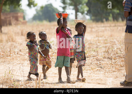 Kisambo Village, Yako, Burkina Faso, 28th November 2016; children bringing shelled ground nuts to women working in the village garden. - Stock Photo