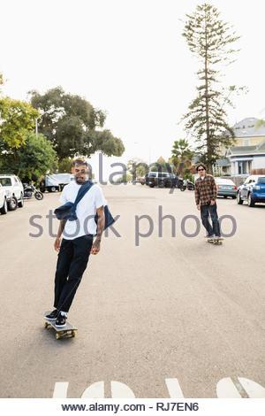 Latinx young men skateboarding on neighborhood street - Stock Photo