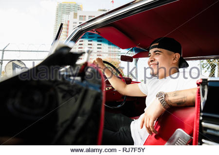 Smiling, confident Latinx young man in vintage car - Stock Photo