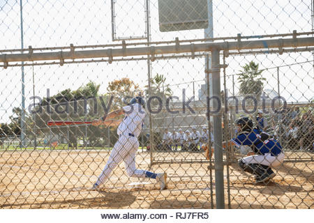 Baseball player at bat on sunny field - Stock Photo