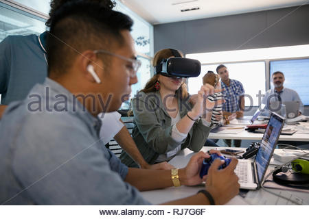 Computer programmers testing virtual reality simulator in office - Stock Photo