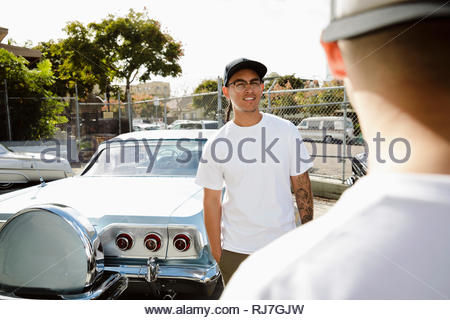 Latinx young man standing next to vintage car in sunny parking lot - Stock Photo