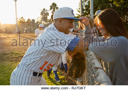 Happy Latinx baseball player talking with girlfriend at fence - Stock Photo