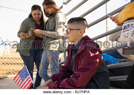 Latinx boy with American flag watching baseball game from bleachers - Stock Photo