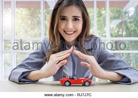 Car insurance concept, Beautiful woman protect her car - Stock Photo