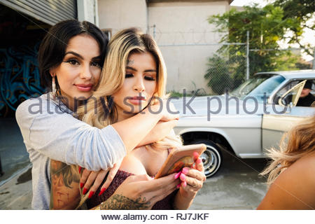 Portrait confident Latinx young woman hugging friend in parking lot - Stock Photo