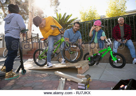 Latinx kids with bikes playing with ramp on sidewalk - Stock Photo
