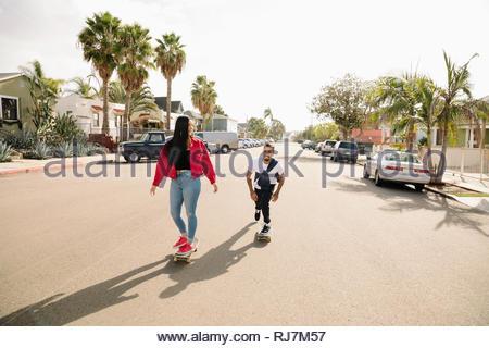 Latinx couple skateboarding on sunny neighborhood street - Stock Photo