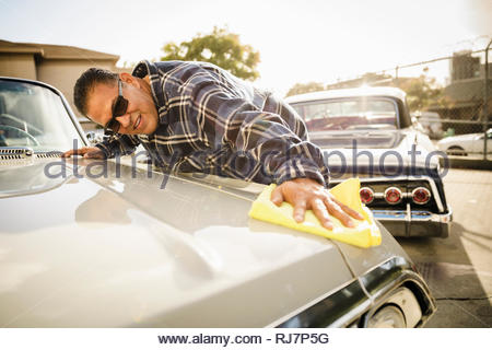 Latinx man waxing vintage car in sunny parking lot - Stock Photo