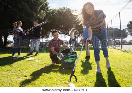 Volunteers picking up garbage in sunny park - Stock Photo