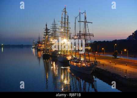 The world largest tall ships berthed in port of Riga, Latvia. Daugava river. Summer night. Dawn. - Stock Photo