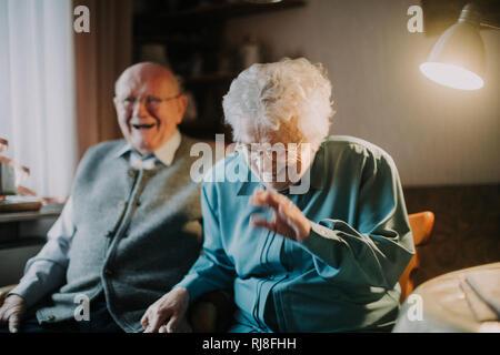 Seniorenpaar sitzt lachend im Wohnzimmer - Stock Photo