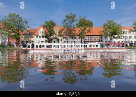 Ausflugsboot auf der Stadttrave mit Blick auf die Altstadt von Lübeck, Schleswig Holstein, Deutschland - Stock Photo
