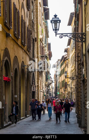 Tourists walking through a narrow alley in the old part of town - Stock Photo