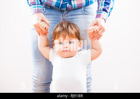 Little boy learning to walk with help from his mother - Stock Photo