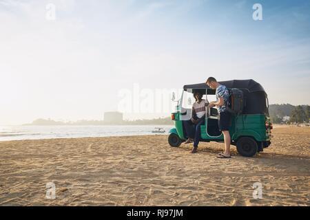 Tuk tuk driver with passenger against sand beach and sea in Sri Lanka. - Stock Photo