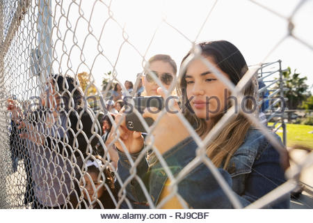 Latinx young woman using smart phone behind fence at baseball game - Stock Photo