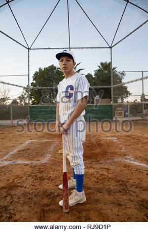 Portrait confident, determined Latinx baseball player with bat on field - Stock Photo
