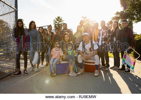 Portrait Latinx family with baseball player in sunny park - Stock Photo