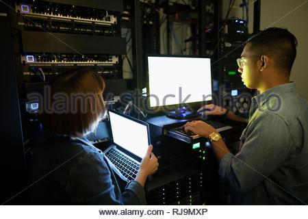 IT technicians using laptops in dark server room - Stock Photo