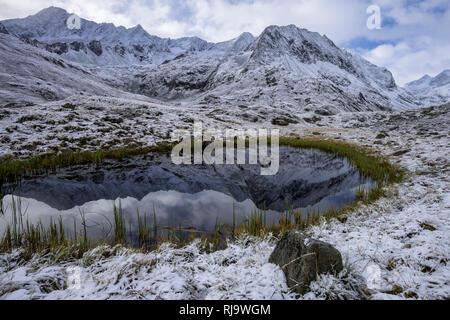 Österreich, Tirol, Stubaier Alpen, Neustift, Oberbergtal, Bergsee in den Alpeiner Bergen nahe der Franz-Senn-Hütte nach dem ersten Schnee im Herbst - Stock Photo
