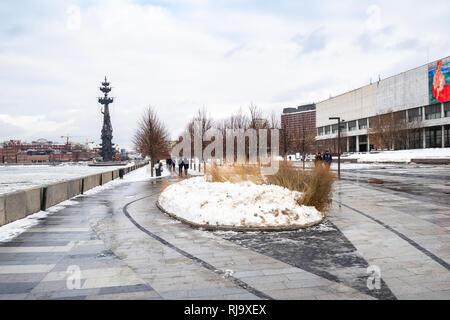 MOSCOW, RUSSIA - JANUARY 18, 2019: people walk on pedestrian Krymskaya embankment near New Tretyakov Gallery of Modern Art and view of The Peter the G - Stock Photo
