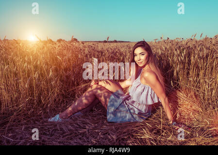 A girl in a wheat field in the summer holds wheat ears in her hand. Sits on the ground. Free space for text. Tanned skin of woman resting in the fresh - Stock Photo