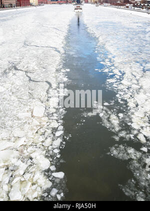 trace of excursion ship in ice of frozen Moskva river along Krymskaya and Prechistenskaya embankments in winter - Stock Photo