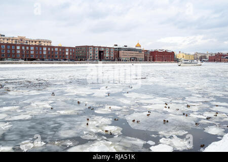 ducks on ice floes in Moskva River and view of Prechistenskaya embankment and Cathedral of Christ the Saviour in Moscow city in winter - Stock Photo