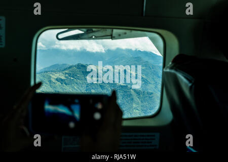 A passenger in an airplane is taking pictures of the beautiful mountainous landscape of Escazu, Costa Rica. Windmills can be seen on the background - Stock Photo