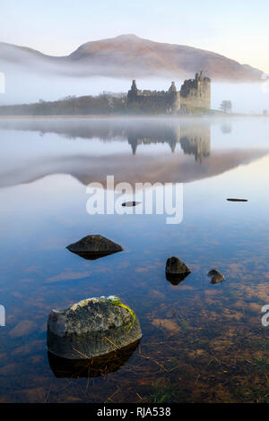 Kilchurn Castle on Loch Awe captured on a misty morning. - Stock Photo