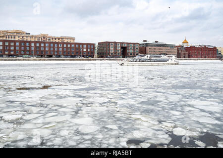 ship swims between ice floes in Moskva River and view of Prechistenskaya embankment and Cathedral of Christ the Saviour in Moscow city in winter - Stock Photo