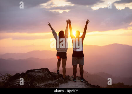 Happy couple with raised arms stands on mountain top against sunset and having fun in winner pose - Stock Photo