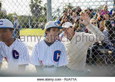 Latinx father talking to baseball player son at fence - Stock Photo