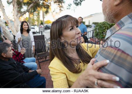 Happy Latinx woman hugging husband on patio - Stock Photo