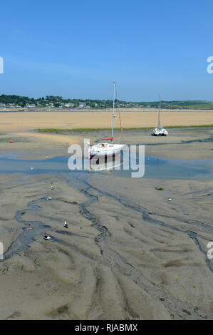 A yacht resting on sand during low tide in the River Camel near Padstow in Cornwall, England. - Stock Photo
